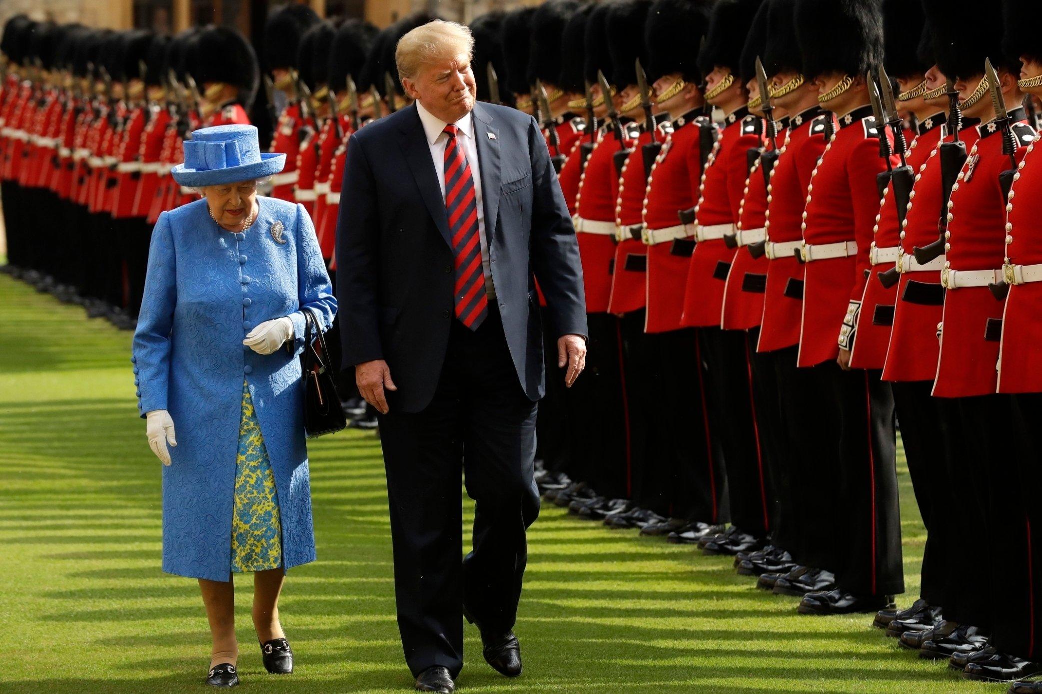 Donald Trump standing in front of the queen